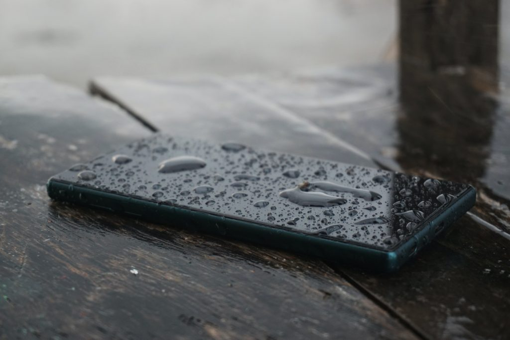 black smartphone on top of brown wooden surface