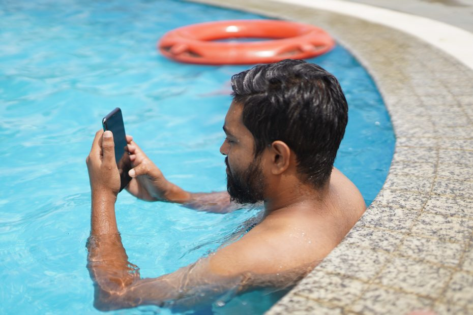 man in swimming pool holding smartphone