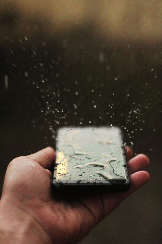 person holding wet iPhone X