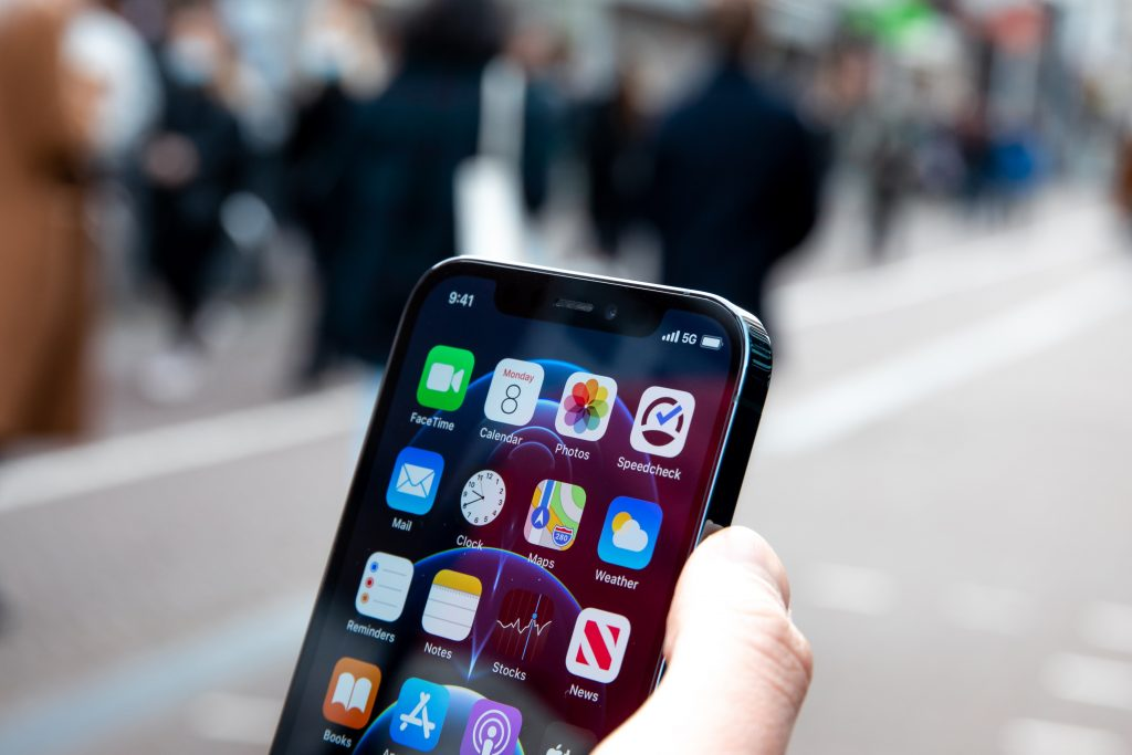 a person holding an iphone on road with blurry background of public