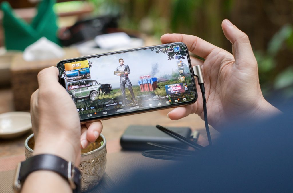 person playing mobile game on iphone